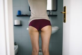 Woman standing in bathroom, close up on the butt.