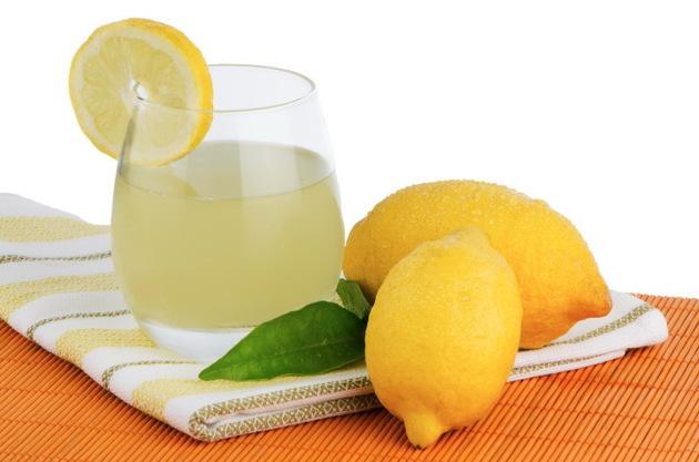 Cup of lemon juice and fresh lemons