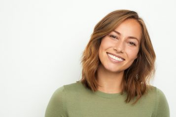portrait of a young happy woman smiling on white background