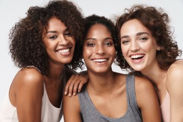 Portrait,Of,Three,Young,Multiracial,Women,Standing,Together,And,Smiling
