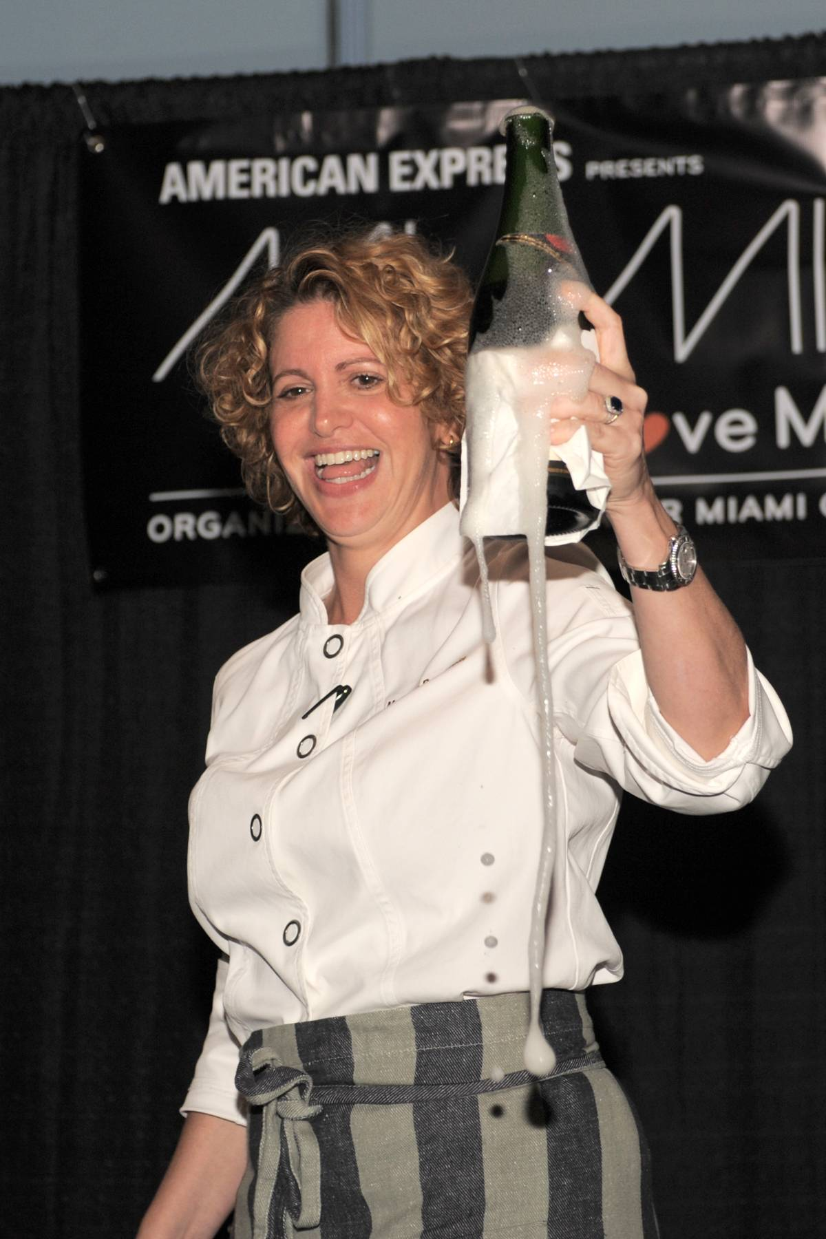 1327-Chef Michelle Bernstein sabers champagne bottle to get festivities popping