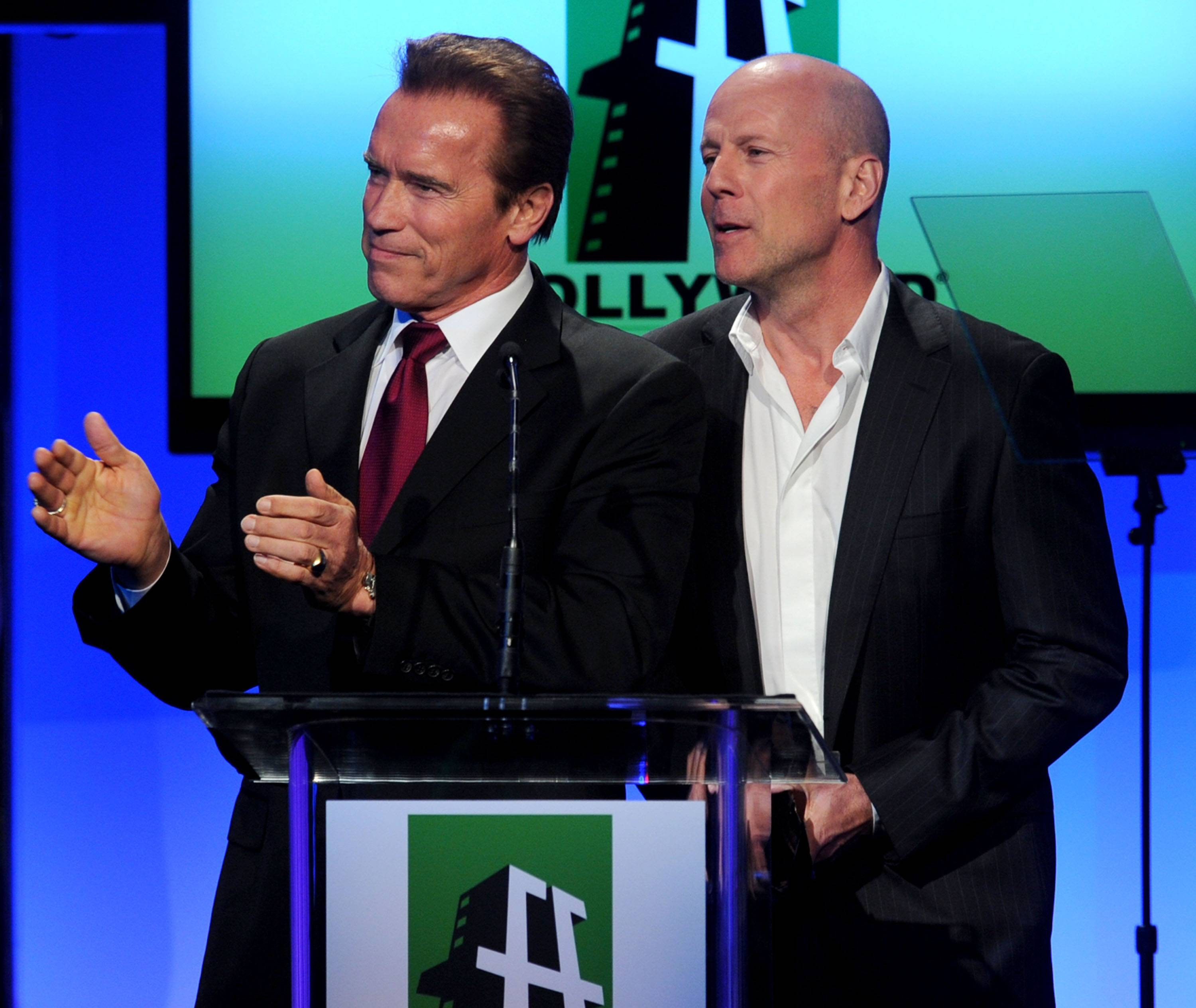 California governor Arnold Schwarzenegger (L) and actor Bruce Willis speak onstage during the 14th annual Hollywood Awards Gala at The Beverly Hilton Hotel on October 25, 2010 in Beverly Hills, California.