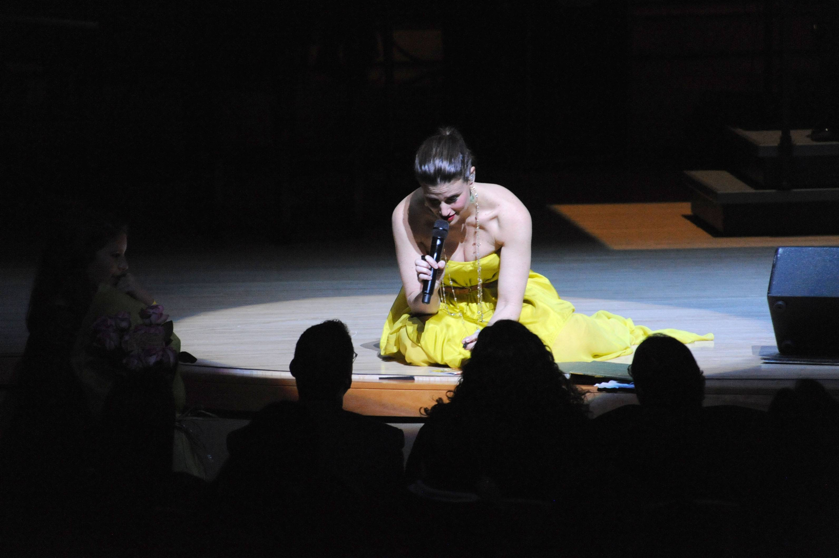 Idina Menzel signing an autograph on stage
