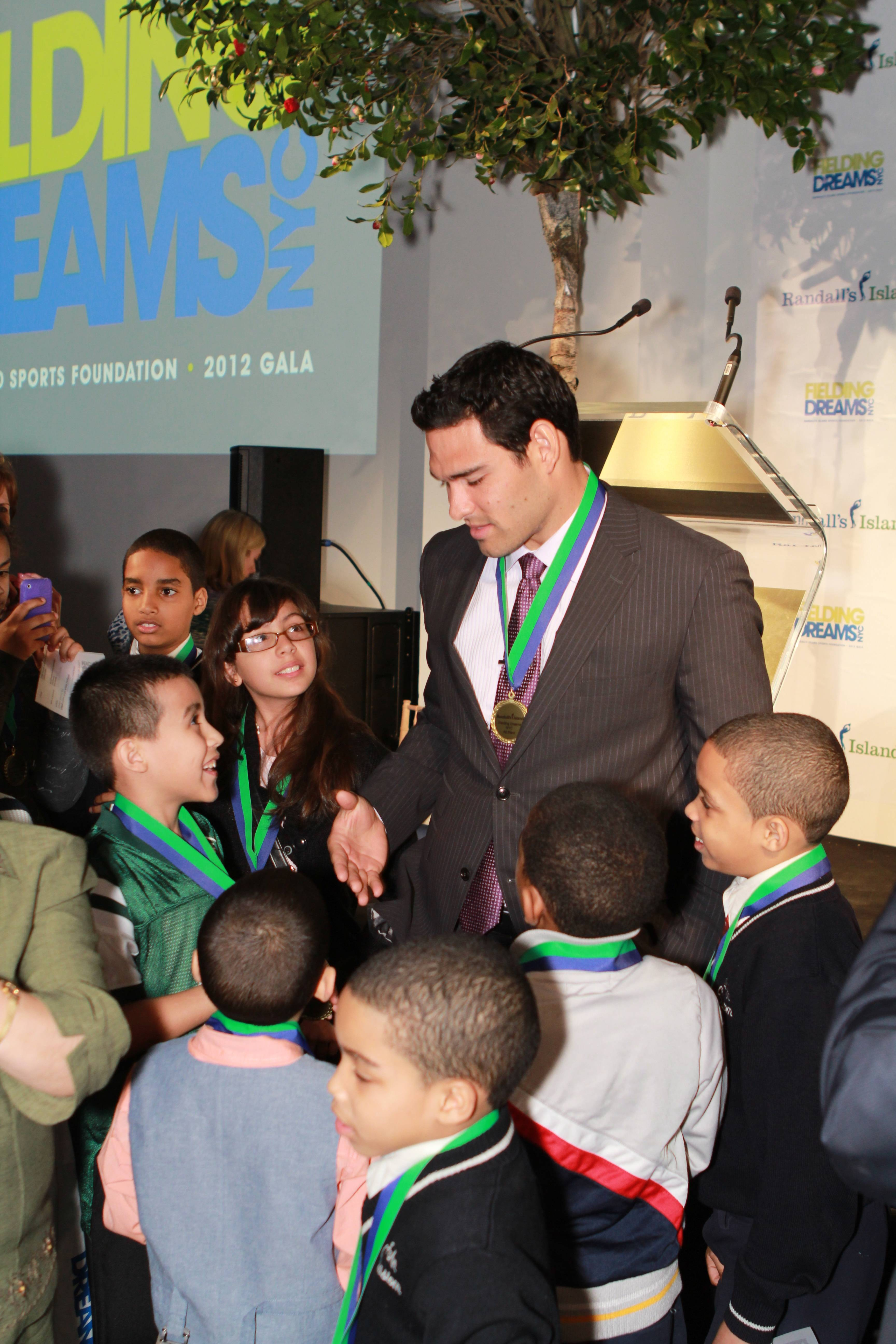 Mark Sanchez with the children from the Casita Maria Center for Arts & Education