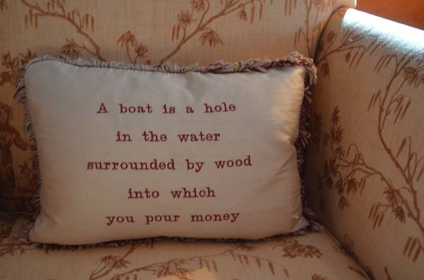 "A pillow on a yacht saying ""A boat is a hole in the water surrounded by wood into which you pour money"""