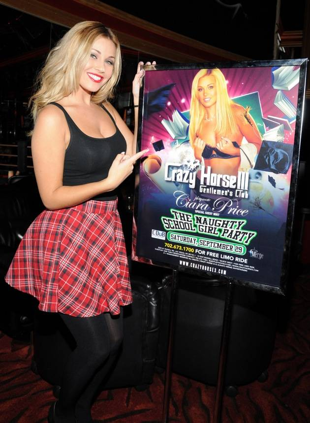 Ciara Price points at her Naughty School Girl event poster at Crazy Horse III.
