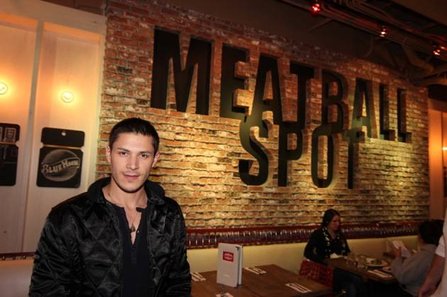 Alex Meraz poses in front of Meatball Spot sign.