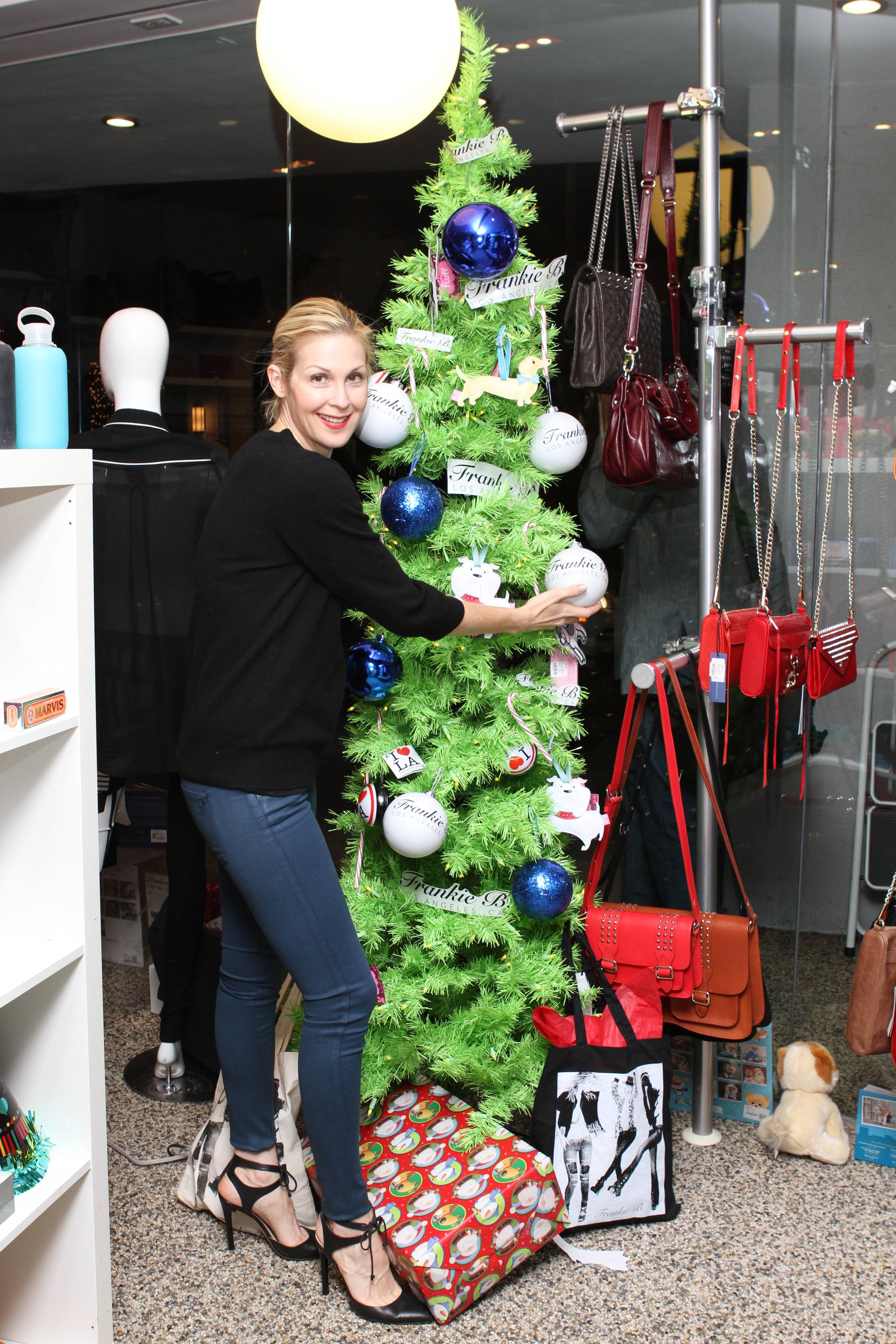 Kelly Rutherford putting a Frankie B ornament on the Kitson tree