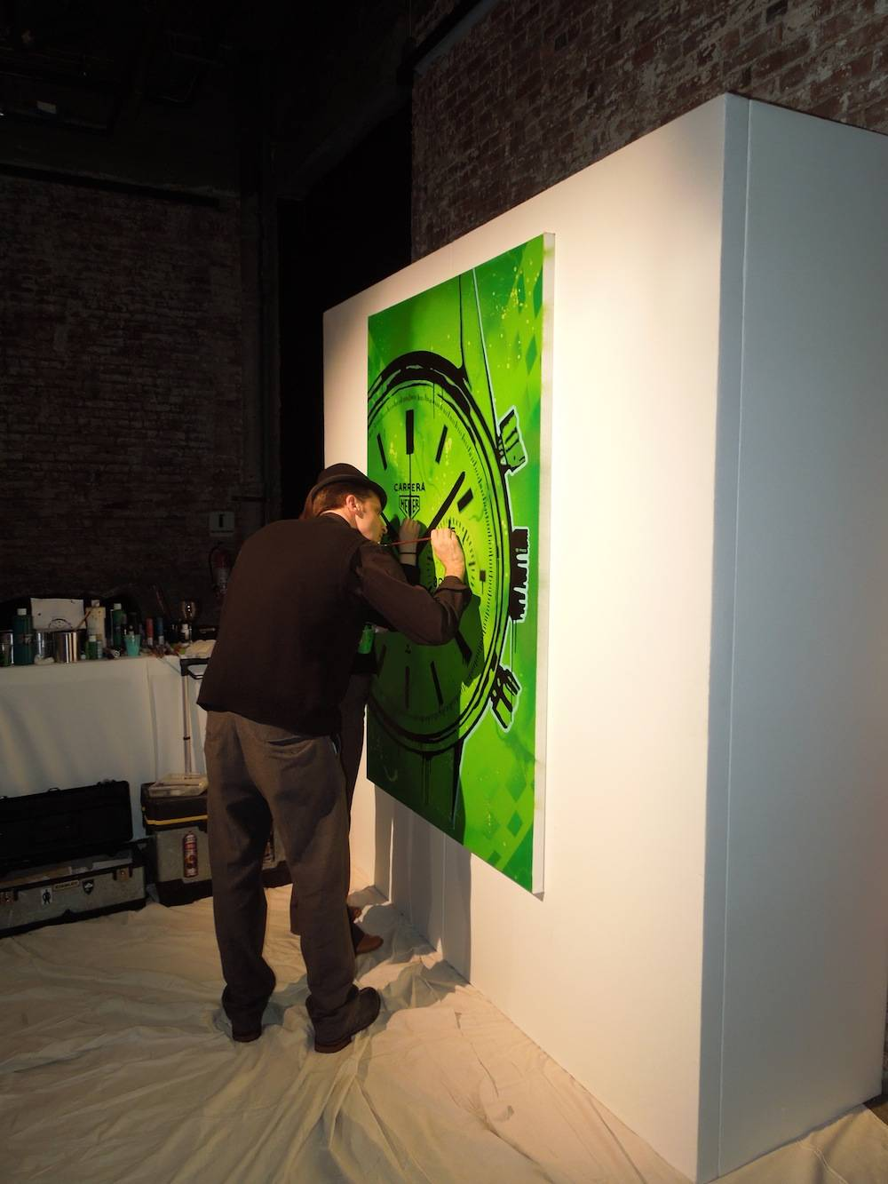 An artist painting a commemorative mural for TAG Heuer Carrera