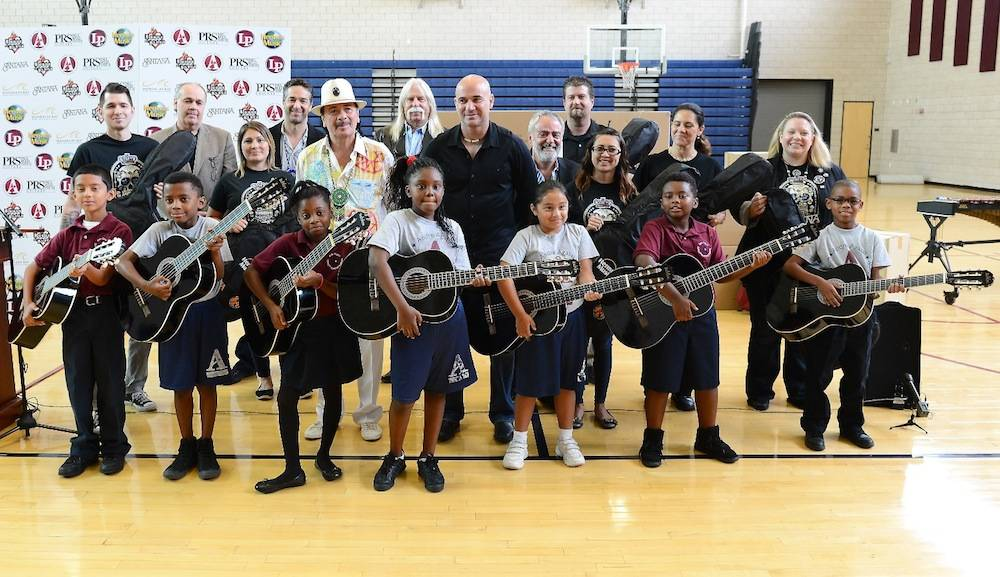 Recording artist Carlos Santana (L) and former tennis player Andre Agassi visit the Andre Agassi College Preparatory Academy to donate more than 200 guitars from Hermes Music and other instruments from LP Music and PRS Guitars for music students on September 10, 2013 in Las Vegas, Nevada. Santana returned to Las Vegas to continue his residency at the House of Blues Las Vegas.