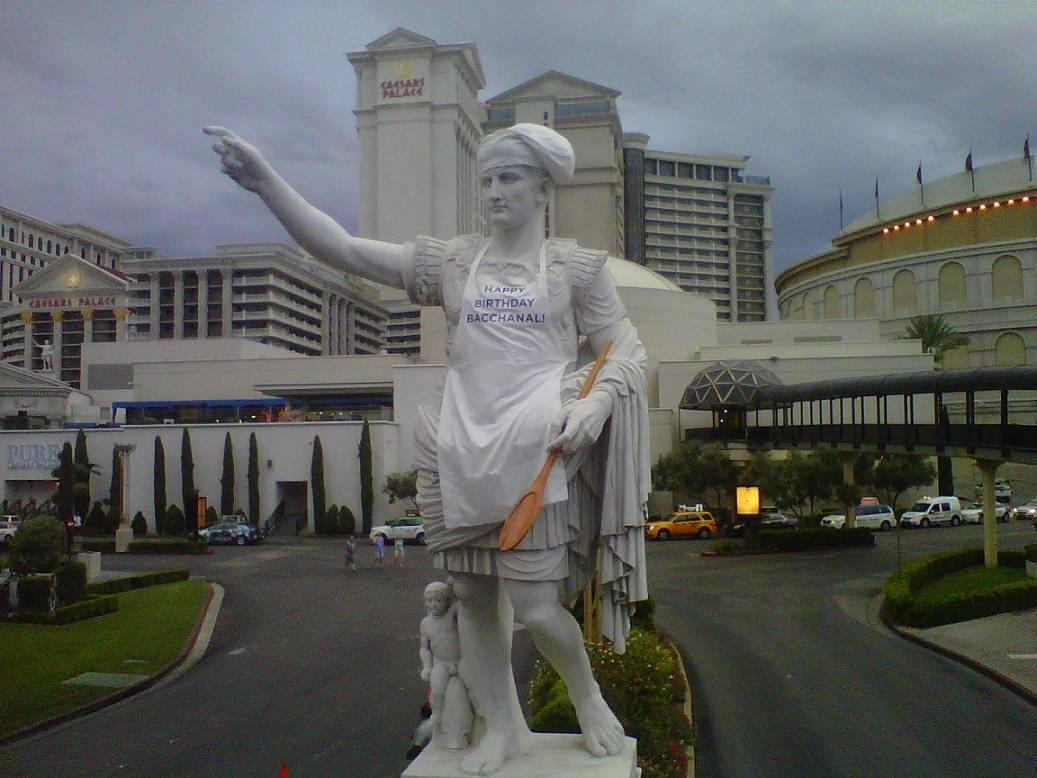 Press.The iconic Caesar Augustus statue wearing chef's hat, apron and spoon