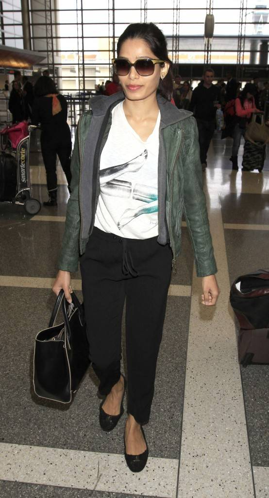 Freida Pinto is all smiles as she strolls through Los Angeles Airport