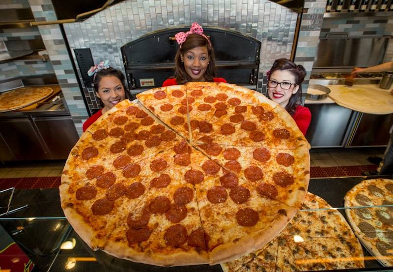 Photo2- It takes three Pin-Up Pizza girls to hold up a 30 inch pepperoni...