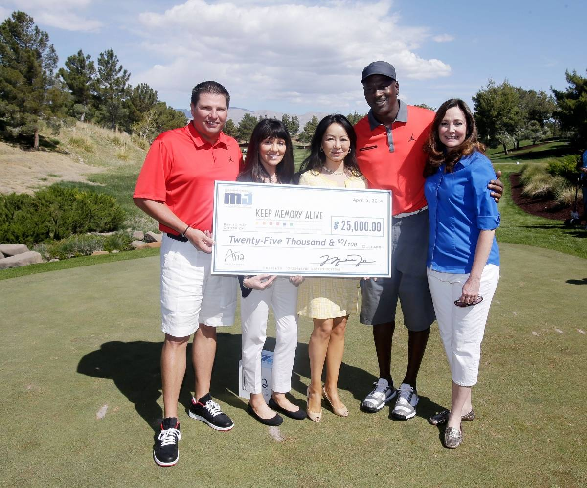 Executive Vice President MGM Resorts International Tyler Shook, (L) Dawn Russi, Kate Zhong, NBA legend Michael Jordan and Gina Hines present a check to Keep Memory Alive