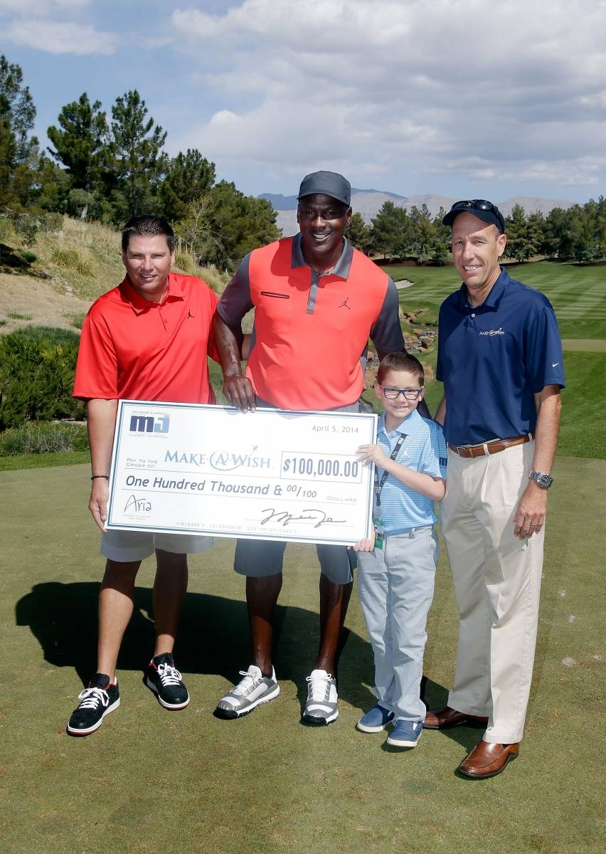 Executive Vice President MGM Resorts International Tyler Shook and NBA legend Michael Jordan present a check to Make-A-Wish Foundation