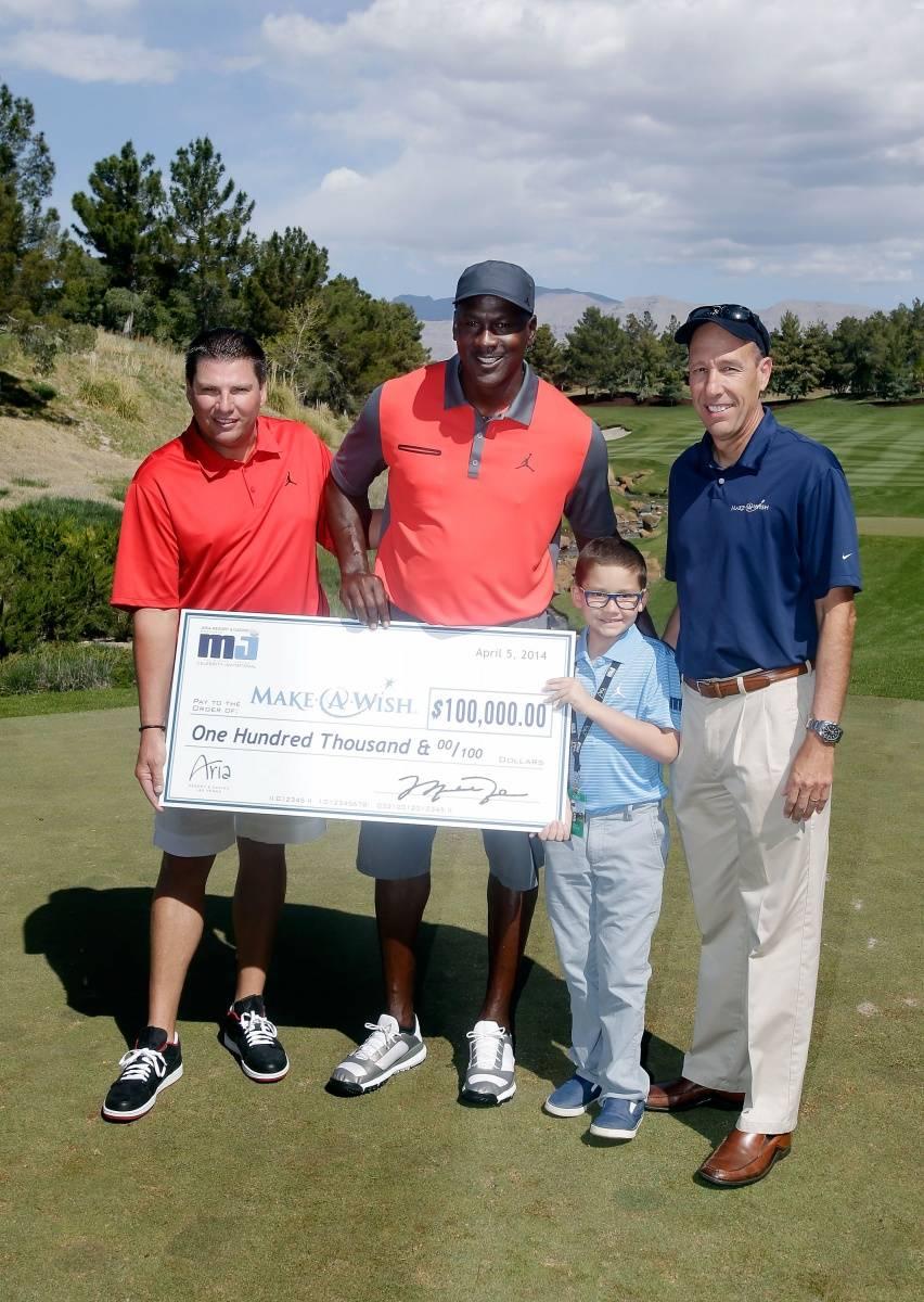 Executive Vice President MGM Resorts International Tyler Shook and NBA legend Michael Jordan present a check to Make-A-Wish Foundation