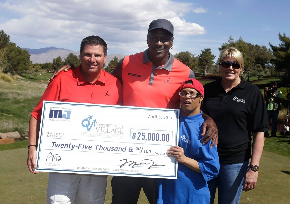 Executive Vice President MGM Resorts International Tyler Shook and NBA legend Michael Jordan present a check to Opportunity Villiage