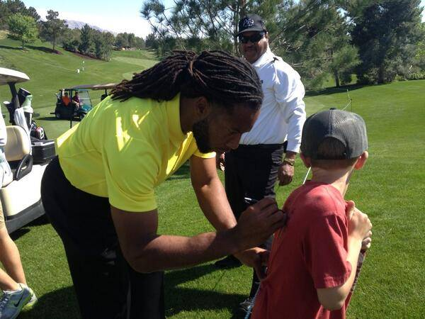 Larry Fitzgerald signing young fan's shirt