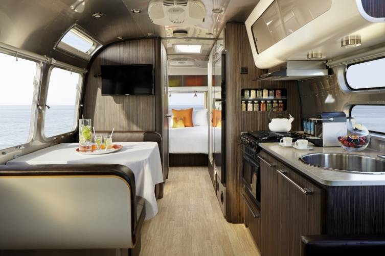 AKA Mobile Suite Interior Kitchen and Bedroom Featuring AKA Luxury Amenities Like AKA's Plush Towels, Linens, and Bathrobe, and Trina Turk California Pillow