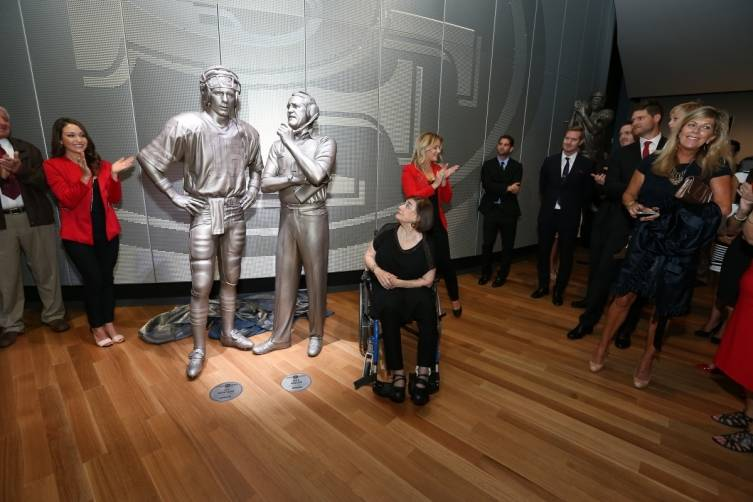 Geri Walsh with statue of Bill Walsh and Joe Montana