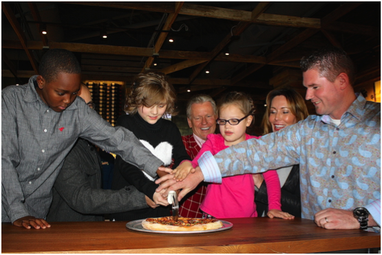 CPK CEO G.J. Hart and General Manager, Clay Wilson are surrounded with loveable Make-A-Wish kids as they slice the ceremonial first pizza and welcome CPK to Downtown Summerlin.