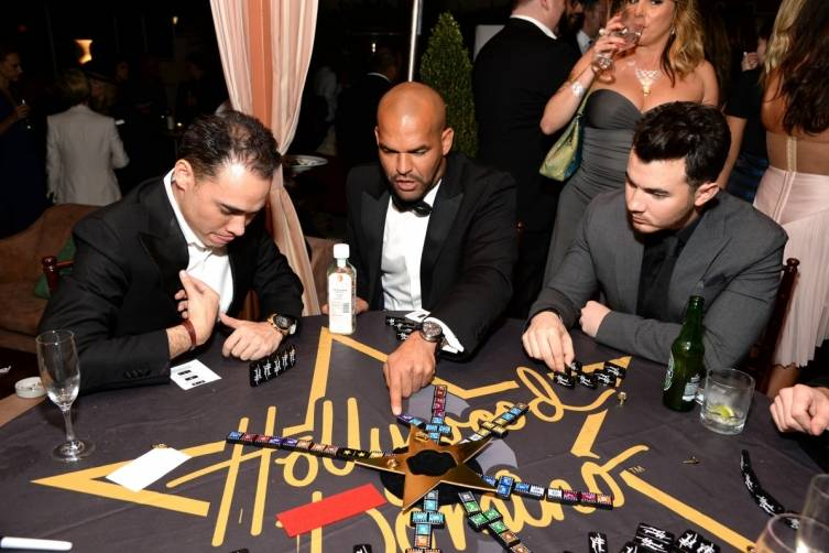 Amaury Nolasco and Kevin Jonas playing dominos