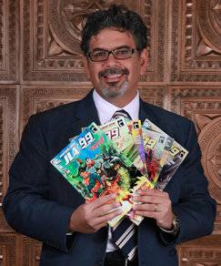 Dr. Naif Al-Mutawa photographed with some copies of The 99, the first group of comic superheroes born of an Islamic archetype, which he created.