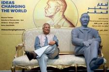 Nobel Peace Prize winner Mohammad Yunus poses with a sculpture of Alfred Nobel at the Nobel Museum's travelling exhibition in Dubai.