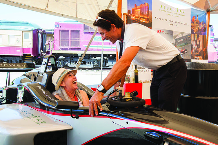 Napa Valley Vintner member Stacey Bressler takes a test sit in the Formula race car part of the St. Supery Live Auction lot display at the Barrel Auction. PHOTO: JASON TINACCI FOR THE NAPA VALLEY VINTNERS
