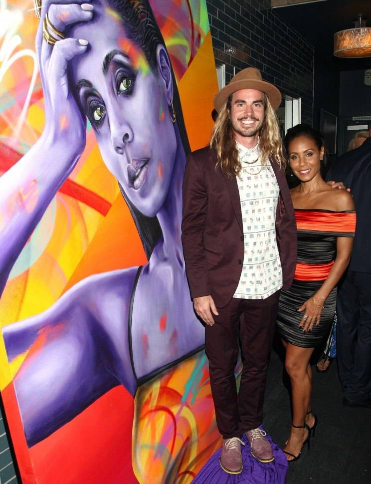 Actress Jada Pinkett Smith poses with a portrait artist Madsteez created in her honor