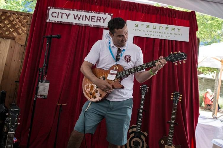Guests are allowed to play various guitars at the City Winery St. Supery display at the barrel auction.
