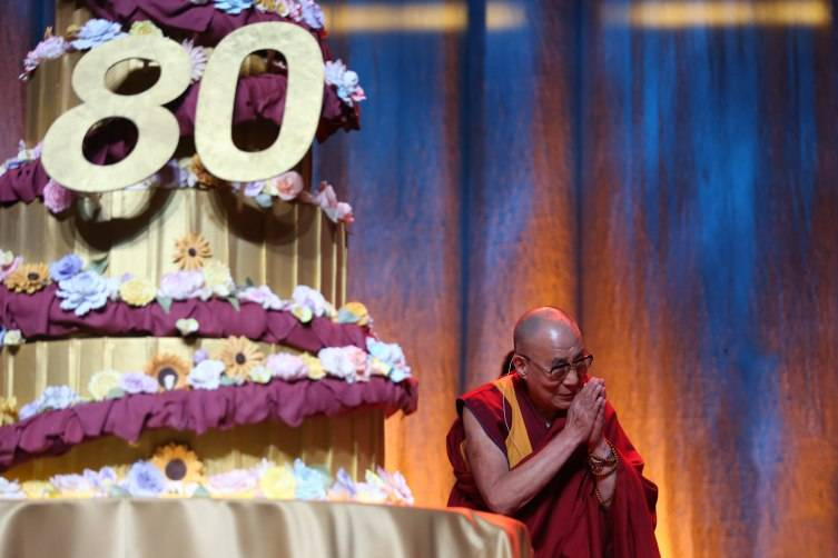 His Holiness the 14th Dalai Lama posing with his birthday cake from the Art Institute of Orange County