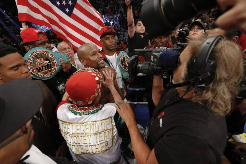 Floyd Mayweather is surrounded by fans after winning his 49th undefeated bout