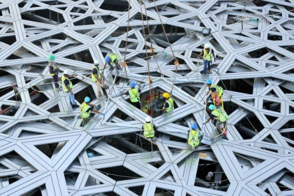 "A handout image from Abu Dhabi Tourism Development & Investment Company (TDIC) made available on September 27, 2015 by the United Arab Emirates News Agency (WAM) shows workers placing the final piece of the outer cladding of the dome structure of the future Louvre museum still under contruction on Saadiyat island, near Abu Dhabi. The museum is expected to open by the end of 2016. AFP PHOTO / HO / WAM == RESTRICTED TO EDITORIAL USE - MANDATORY CREDIT ""AFP/HO/WAM"" - NO MARKETING NO ADVERTISING CAMPAIGNS - DISTRIBUTED AS A SERVICE TO CLIENTS =="