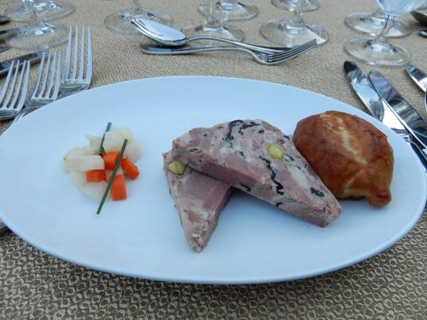Duck confit, duck ham, and & ris de veau terrine flavores with pistachios, homemade pretzel bun