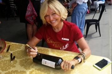 Kathryn Walt Hall signs a bottle