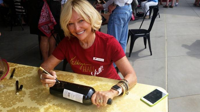 Kathryn Walt Hall signs a bottle of her 97-point