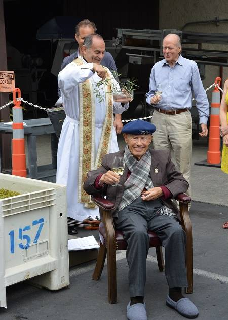 Mike Grgich smiles as Father Gordon of St. Helena Catholic Church sprinkles a bit of divine water on him at the Blessing of the Grapes ceremony to celebrate Grgich Hills Estate's 39th harvest.
