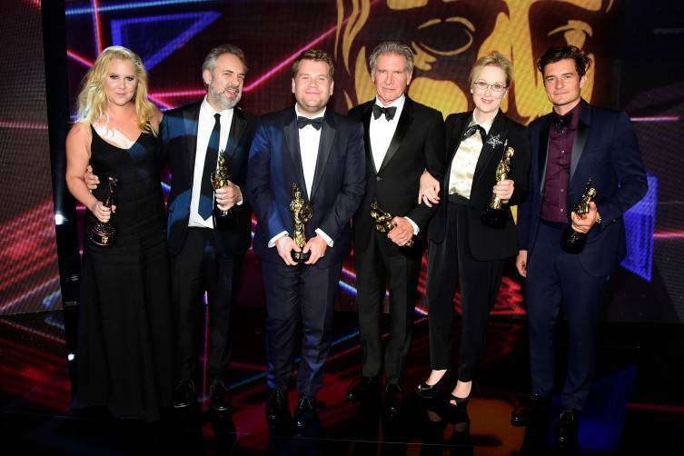 Honorees (L-R) Amy Schumer (holding the Charlie Chaplin Britannia Award for Excellence in Comedy presented by Kodak), Sam Mendes (holding the John Schlesinger Britannia Award for Excellence in Directing presented by The GREAT Britain Campaign), James Corden (holding the Britannia Award for British Artist of the Year presented by Burberry), Harrison Ford (holding the Albert R. Broccoli Britannia Award for Worldwide Contribution to Entertainment), Meryl Streep (holding the Stanley Kubrick Britannia Award for Excellence in Film) and Orlando Bloom (holding the Britannia Humanitarian Award presented by The Beazley Group) pose onstage during the 2015 Jaguar Land Rover British Academy Britannia Awards