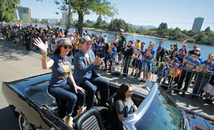 Nicole Curran and Joe Lacob ride in the championship parade in Oakland