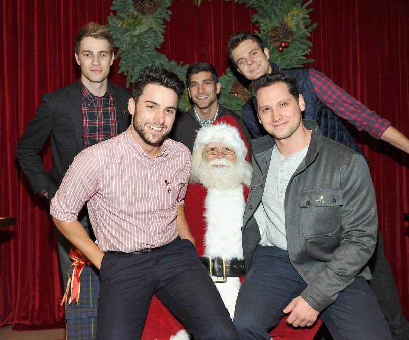Actors Cameron Fuller, David Bernon and Jack Quaid, (bottom L-R) Actors Jack Falahee and Matt McGorry pose with Santa Claus at the Brooks Brothers holiday party