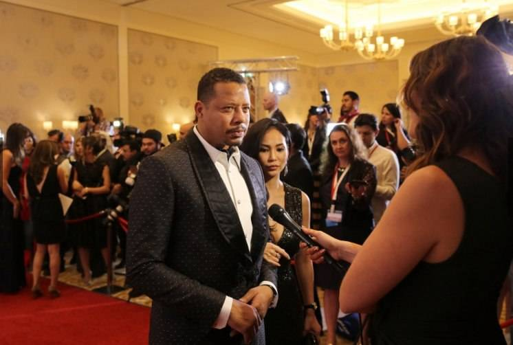 Terrence Howard is interviewed at the Global Gift Foundation Gala Dinner as his wife Miranda listens in.