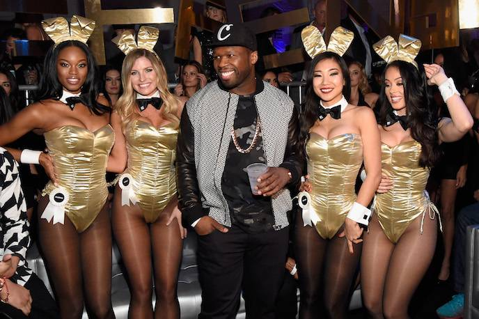 Rapper and entrepreneur 50 Cent (C) arrives at the The Playboy Party during Super Bowl Weekend with Playboy Playmates Eugena Washington, Carly Lauren, Hiromi Oshima and Ashley Doris wearing Bunny costumes inspired by the gold detailing on his limited edition EFFEN Vodka football bottle.