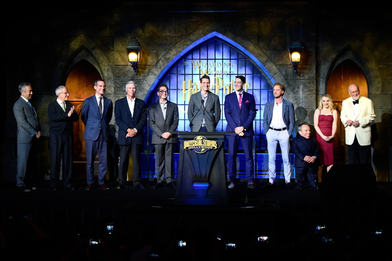 Chairman and CEO of Warner Bros. Entertainment Kevin Tsujihara, vice chairman of NBC Universal Ron Meyer, mayor of the city of Los Angeles Eric Garcetti, chairman and CEO, Universal Parks and Resorts Tom Williams, president, Universal Studios Hollywood Larry Kurzweil and actors James Phelps, Oliver Phelps, Tom Felton, Warwick Davis, Evanna Lynch and composer John Williams speak onstage at the opening of the 'Wizarding World of Harry Potter' at Universal Studios Hollywood