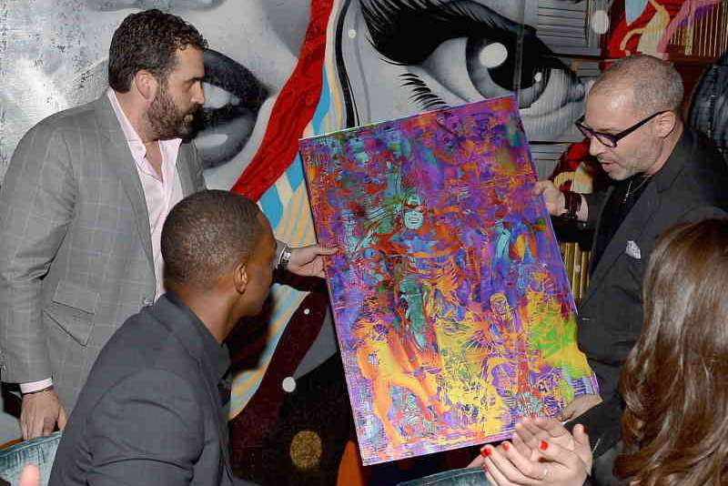 Paul Gerben presents Anthony Mackie with the Captain America painting he created in his honor