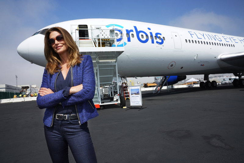 Cindy Crawford stands in front of the Orbis jet