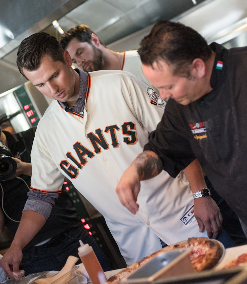 Joe Panik learns how to sprinkle cheese on pizza from Tony Gemignani.