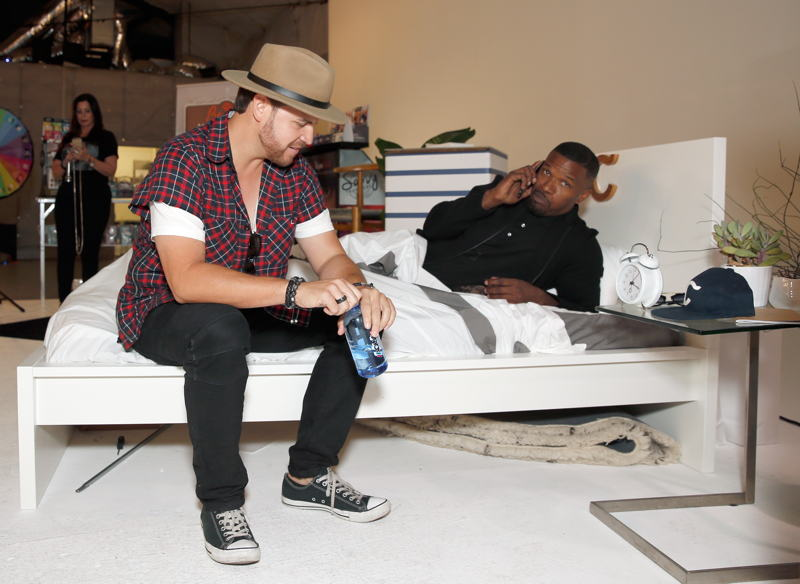David Osokow (L) and actor/singer Jamie Foxx lounging on a Casper bed at Kari Feinstein's Style Lounge at Siren Studios