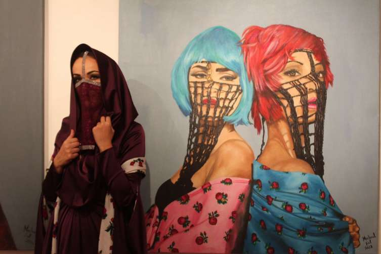 Egypt Show - Mashael next to her painting entitled twins