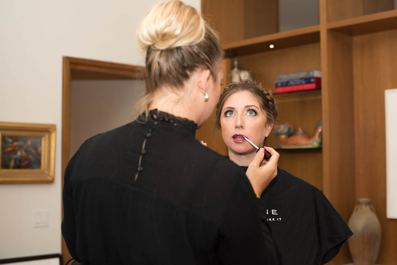 A La Mienne makeup artist adds a finishing coat of glass